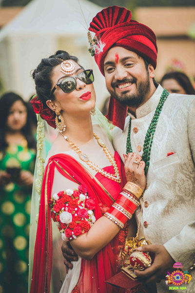 Chitrakshi and Neil | Offbeat wedding in Delhi | Day wedding full of ideas | Indian bride wearing an ivory lehenga with a floral sleeve blouse and a red and pista pastel double dupatta | Indian bride and groom at the wedding | groom wearing ivory sherwani with a red pocket square and green emerald strings | Indian bride pouting in sunglasses | photo by Design Aqua | WIttyVows