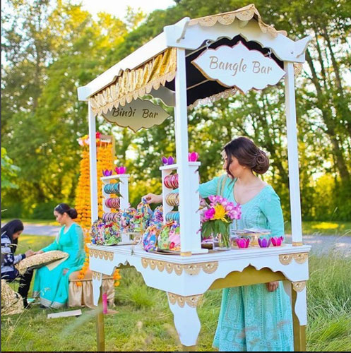 Teej party ideas | Teej Celebrations | Indian Mehendi with a bangle bar for favours |white cart with pretty signage and favours for guests