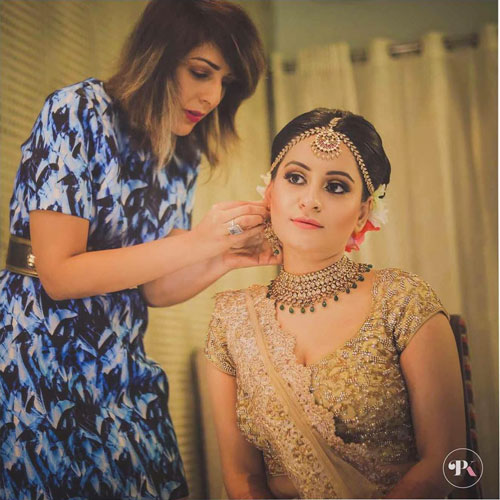 Best Bridal Makeup Artists in Delhi, bride getting ready in golden lehenga by Pooja Khurana