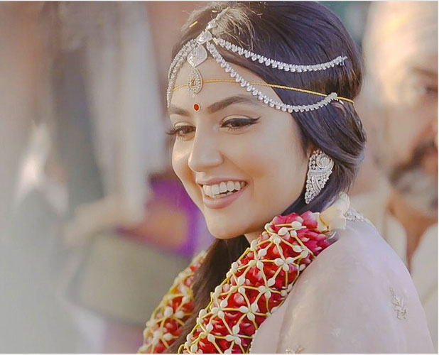 pretty bride wearing a diamond mathapatti with a stunning red and white jaimala | photo by colorblind productions