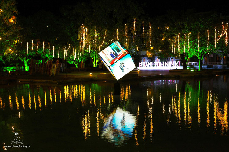 Nindiya and Nirmal | Indian bridal lehenga | Real flower lehenga | The LED box decor with the pictures of the bride and groom and its refelection in the water looks so gorgeous.