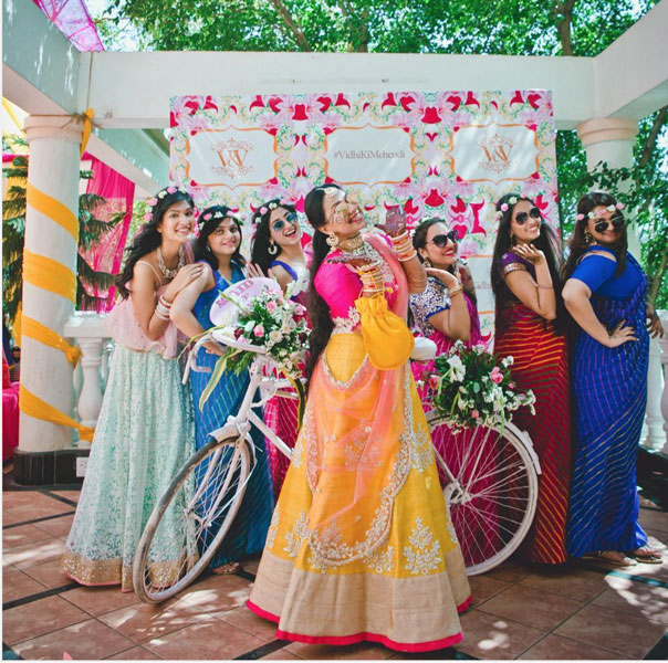 Squad accessories for Indian Weddings | Team bride metallic Badge that you can use | Ideas for the bride's side bridesmaids | Team bride Indian bridesmaids wearing matching flower crowns posing behind the bride at the mehndi | indian bride wearing a pretty gold and orange lehenga with a pink blouse | Indian bridesmaids photoshoot idea
