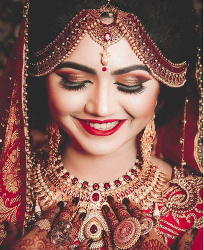 red coloured mathapatti | stunning indian bride | happy bride wearing traditional red an gold bridal jewellery