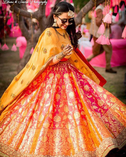 New lehenga styles, Gorgeous lehenga ideas, Unique lehengas | Bhumi and Simran Photography | Indian bride toiling in her benarsi lehenga | bride in a red and yellow ombre benarsi lehenga with gold handwork in Zari wearing sunglasses