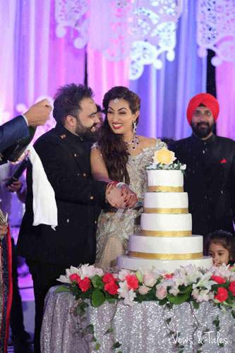 Bavleen and Kushal | Destination wedding in Goa | The bride and groom share a happy moment while cutting the six layered reception cake.