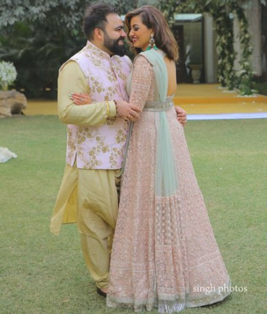 Bavleen and Kushal   Destination wedding in Goa   The bride in a pink gown and the groom in a beige colored sherwani looking in each oher's eyes.