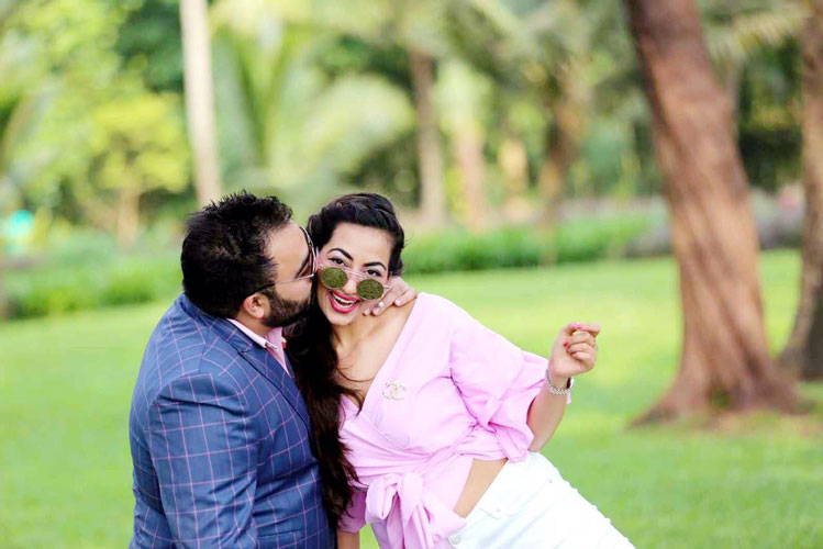 Bavleen and Kushal   Destination wedding in Goa   The bride in a baby pink, offshoulder outfit getting a peck from her groom in a tuxedo.