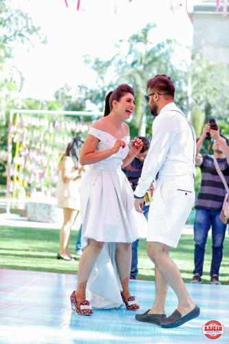 Netika and Kushank | Destination wedding in Jaipur | The bride in her offshoulder skirt gown and the groom in his comfy white shorts dancing together.