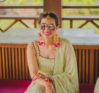 Bavleen and Kushal | Destination wedding in Goa | The bride loks beautiful in her mehendi outfit of sea green color with her shades on.