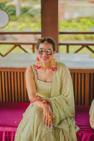 Bavleen and Kushal   Destination wedding in Goa   The bride loks beautiful in her mehendi outfit of sea green color with her shades on.