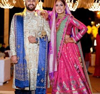 Netika and Kushank | Destination wedding in Jaipur | The bride in a banarsi lehenga with her groom wearing a white sherwani.