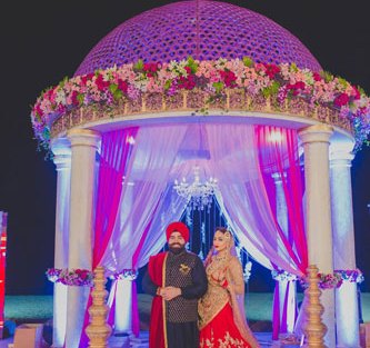 Bavleen and Kushal | Destination wedding in Goa | The bride and groom in front of the mandap posing together.