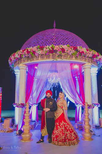Bavleen and Kushal   Destination wedding in Goa   The bride and groom in front of the mandap posing together.