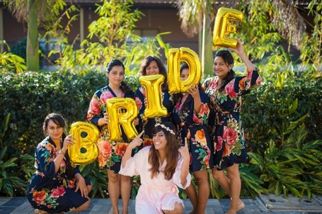 Joshua and Shona   Christian wedding   DIY ideas   The bride tribe wearing matching robes and posing with cute foil baloons while the bride smiles in a white robe and tiara.