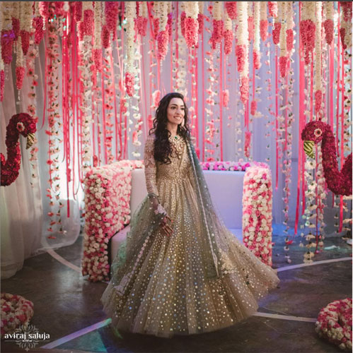 Jaya standing in front of a super pretty flamingo Photo Booth with white and pink flower strings in a pretty gold and green Tarun tahiliani suit