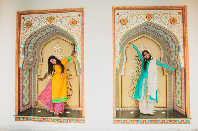 Nimisha and Hemant | Temple wedding in Delhi | The bride in her yellow outfit posing with her friend in a green outfit.