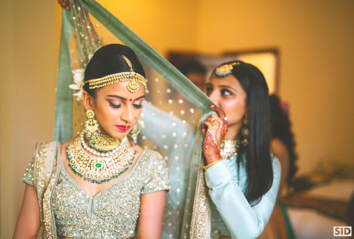 indian bride getting ready | bride in a pretty pale pastel green and gold blouse wearing a Kundan and emerald bridal set | bridesmaid draping the dupatta on the bride | total Sid photography