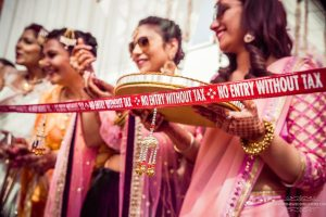 Baraat welcome ideas | sister of the bride with a. and entry banner for the groom | fun Indian wedding ideas