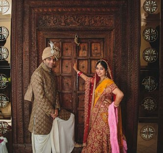 Nimisha and Hemant   Temple wedding in Delhi   The bride and the groom giving a royal pose in front of the vintage wooden door.