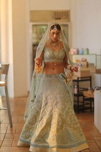 Bride wearing a light pastel blue and mint green and gold lehengas with a sheer single dupatta walking to the wedding | dupatta draping ideas | photo by the light smiths