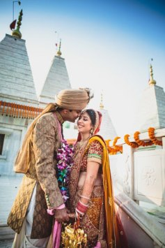 Nimisha and Hemant | Temple wedding in Delhi | The bride and groom share a happy moment in the backdrop of temple after their wedding.