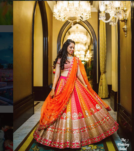 Bride wearing a pretty red to yellow ombre Banarasi lehengas with a pretty saree style bridal dupatta drape | photo - wedding salad