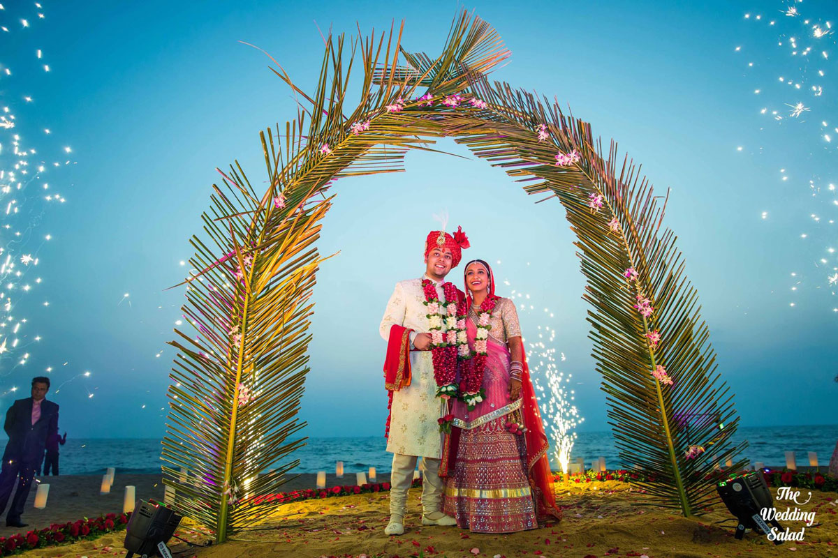guide to planning a beach wedding in india   Goa wedding with bride and groom standing under a plan leaf gate with sparklers