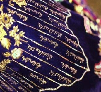 bride aakanksha's custom lehenga with her name and her finance's name embroidered on a blue lehenga