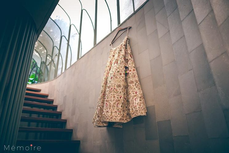 Khushboo and harshang - Gujarati wedding with fun wedding ideas | Creme bridal lehengas with red and green and gold embroidery hanging on a hanger