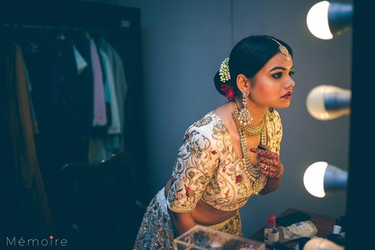Khushboo and harshang - Gujarati wedding with fun wedding ideas | bride iin a creme lehengas getting ready for the wedding