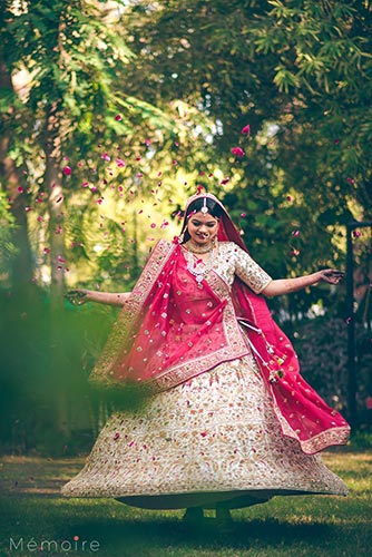 Khushboo and harshang - Gujarati wedding with fun wedding ideas | bride in a creme lehengas with red and green embroidery paired with a red dupatta