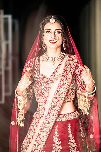 aditi and Rohan | Delhi weddng for a model bride | plush affairs photography | bride in a red lehengas and gold and red blouse in dab with Kundan jewellery