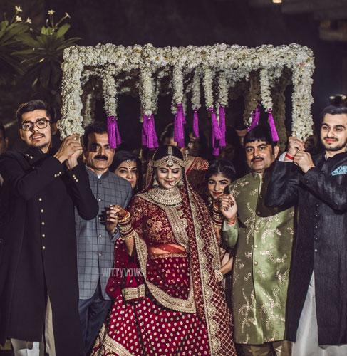 Wedding in Ahmedabad in Ahmedabad | bridal entry | bride in red Sabyasachi lehenga | white chadar with purple tassels