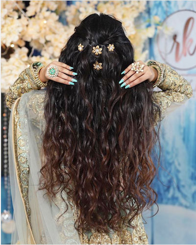 crimped hair messy curls with a half upto and floral clips dewlap party hairstyles