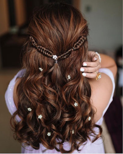 fishtail braid half upto with small dispersed flowers in the hair