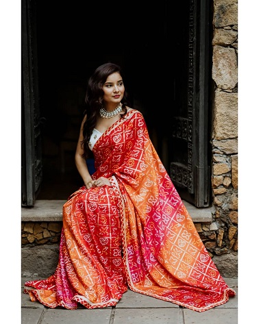 Bandhej saree in red and orange paied with a white crop top | Trending new fashion ideas | Fashion influencers | Saree love |  Sari inspiration |