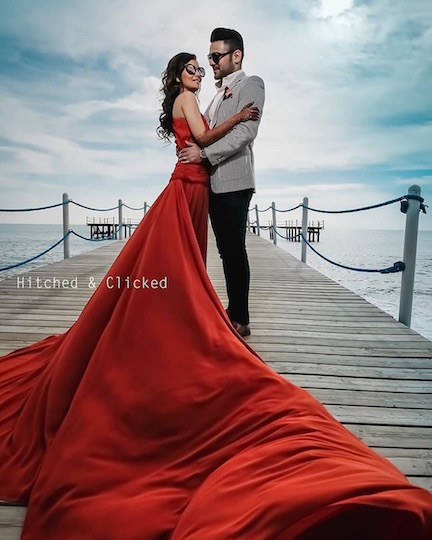 red cocktail gown | wedding shoot | indian couple | indian wedding | leo bridal fashion | leo zodiac bridal style | couple by the sea photography | leo bridal fashion | bridal style for leo sun sign | zodiac sign | wedding dress for your zodiac sign | indian wedding | indian bride in red gown | modern indian bride | #bridesofwittyvows #indianwedding #inidanbride #indianbridecrying #bridalgown #weddingdressforyourzodiacsign #mehendidesigns #wittyvows #zodiacfashion #zodiacsign #zodiacbridalstyle #leosunsign #leobride #leoindianbride #modernindianbride