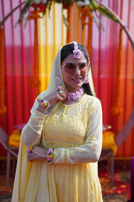 indian bride posing for pictures at her mehendi ceremony