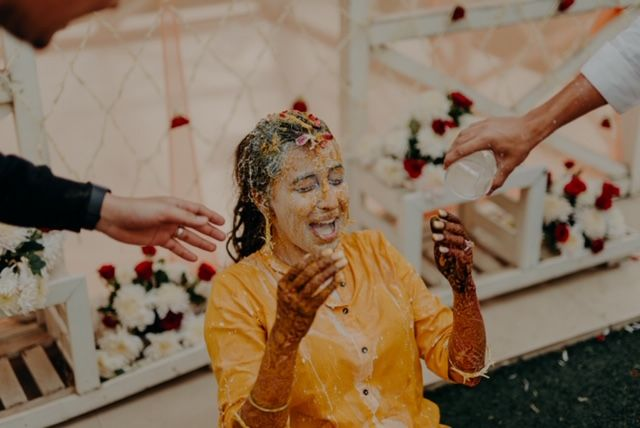 bride immersed in haldi and water