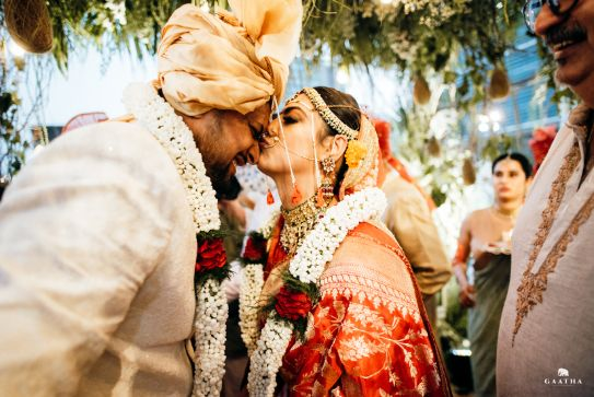 bride kissing the groom | varmala ideas to steal from \ eco friendly wedding