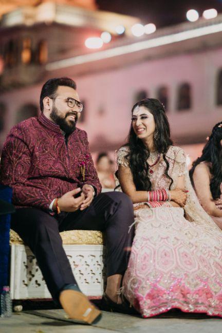 groom in maroon outfit, bride in p astel pink lehenga | Destination Wedding in Udaipur
