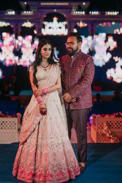 bride in pastel pink lehenga | groom in matching maroon coat | Destination Wedding in Udaipur