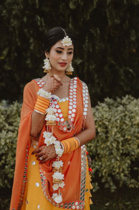 bride in yellow and orange for her haldi ceremony