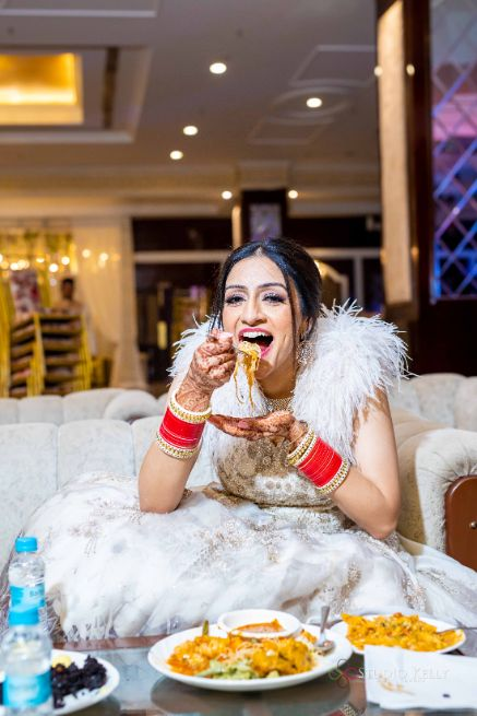 indian bride enjoying some food | Stunning Reception Look