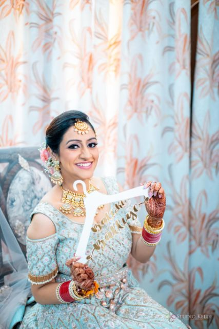 indian bride posing with customized bridal namehanger | Pastel Wedding with a Stunning Reception Look