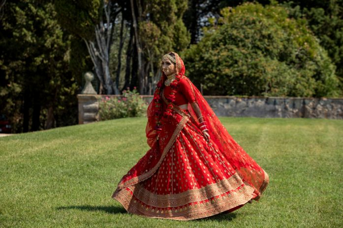 twirling sabyasachi bride | indian couple photoshoot | indian bridal portrait | red chooda bridal wear accessories | Destination wedding in Italy & Red Sabyasachi lehenga sikh wedding nri indian weddings #wittyvows #indianbride