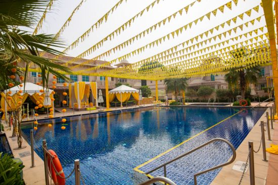 pool side wedding | indian wedding pool side | destination wedding outside delhi | haldi ceremony | floral decoratioms | indian parents and bride | realwedding |  Kitsch mehendi decor