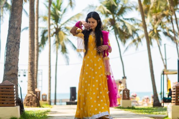 bride in stunning yellow outfit with pink dupatta