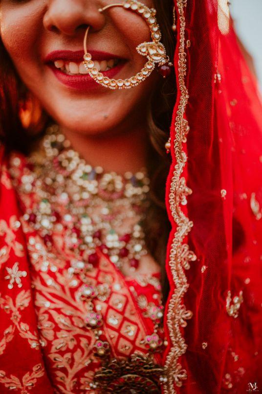 bridal portrait , red lehenga , couple kissing , indian groom , Rajasthani wedding | DIY lehenga design | Bridal hairdo | footear | boss bride customised | wittyvows real wedding |