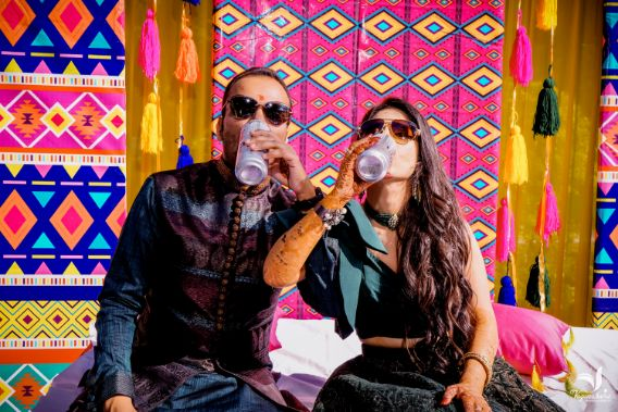 couple drinking , indian bride drinking , indian bride candid , mehendi function , green lehenga , indian wedding , wedding blog , indian couple , wittyvows , lehenga , indian bride off shoulder gown | mehendi outfit | pre wedding shoot in greece , pink chooda
